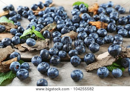 Tasty ripe blueberries with green leaves on wooden table close up