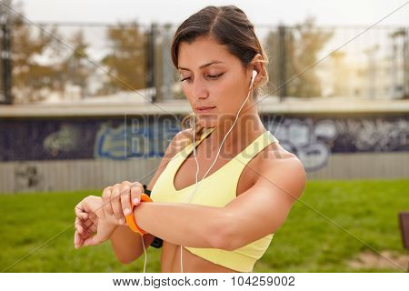Young Athlete Looking At Smart Watch Outdoors
