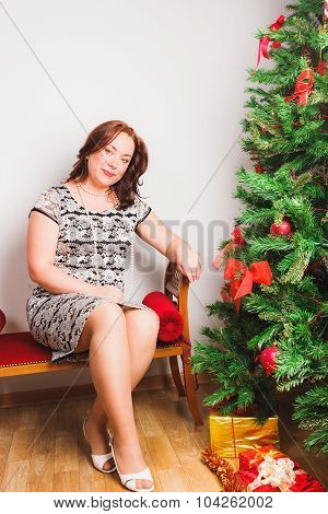 Happy woman sits nearby Christmas tree