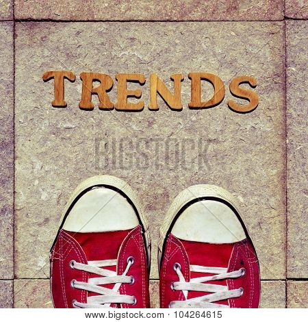 high-angle shot of some wooden letters forming the word trends and the feet of a man wearing red sneakers on the street
