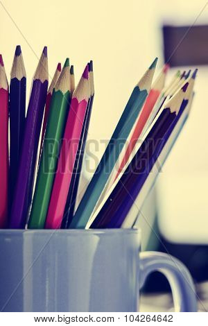 closeup of a blue mug with many coloured pencils of different colors, on a desk, with a filter effect