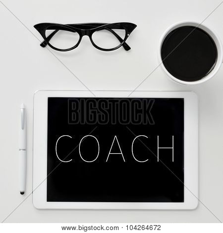 high-angle shot of a desk with a tablet computer with the word coach written in it, a pair of women eyeglasses and a cup of coffee