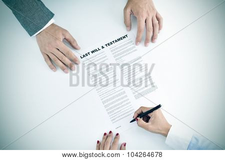 high-angle shot of a young woman signing a last will and testament document in front of a young man