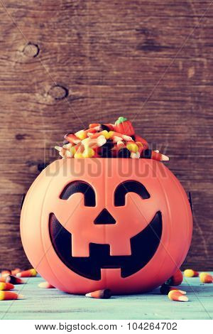 a carved pumpkin full of different halloween candies on a rustic blue wooden surface