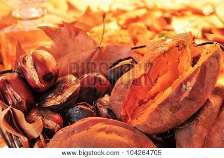 closeup of a rustic basket with some roasted chestnuts, some roasted sweet potatoes and autumn leaves