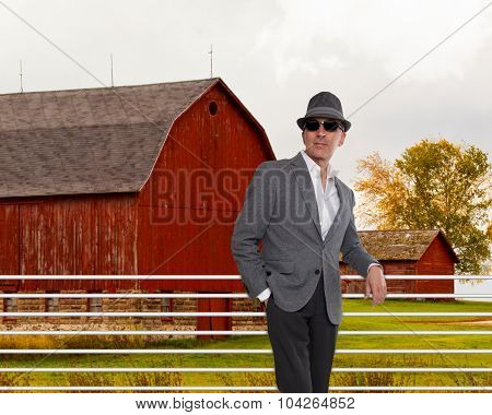 Fashionable man standing in from of a red barn