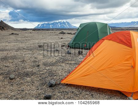Camping tents on a rocky campsite in Iceland with Herdubreid in background