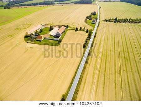 Aerial view to fields with farm house and road.