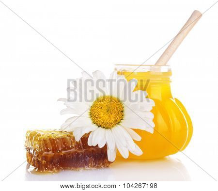 Pot of honey with wooden dipper, honeycomb and chamomile isolated on white