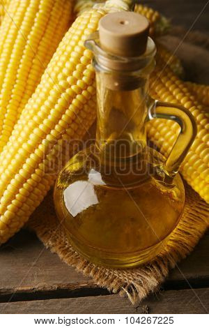 Fresh corn with bottle of oil on table close up