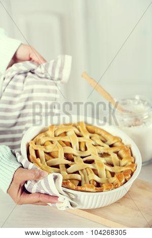 Homemade apple pie  in female hands, on light background