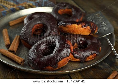 Delicious doughnuts with chocolate icing and cinnamon on metal tray close up