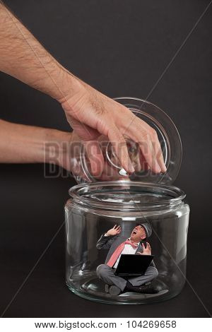 Businessman trapped inside a transparent glass jar