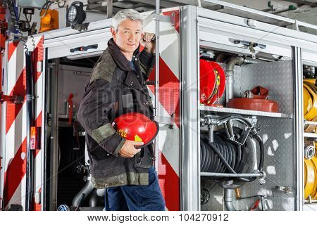Portrait of confident fireman in uniform standing on fire engine at station