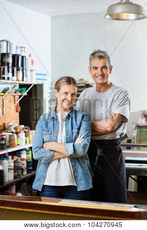 Portrait of confident male and female workers standing arms crossed at stencil in paper factory