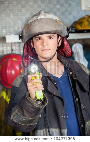 Portrait of confident male firefighter holding torch at fire station