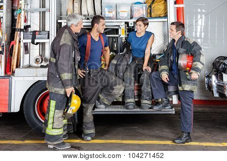 Team of male and female firefighters conversing by firetruck at station