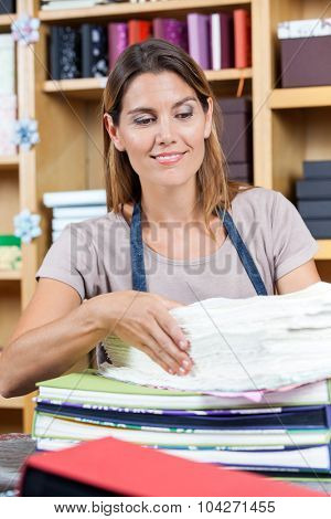 Mid adult female worker analyzing papers while smiling in shop