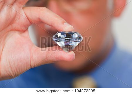 Close up of a hand holding a big fake diamond