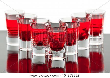 Beautiful shot crystal glasses with red liquid