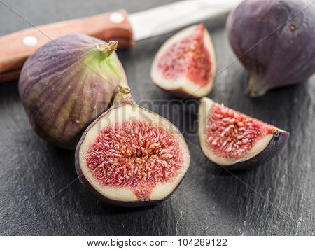 Ripe fig fruits on the graphite cutting board.