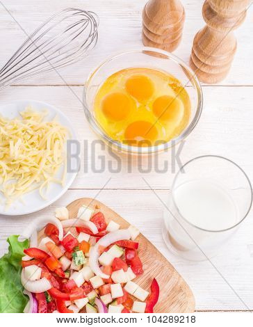 Omelette ingredients: eggs, fresh cut vegetables, milk and cheese on the wooden table.