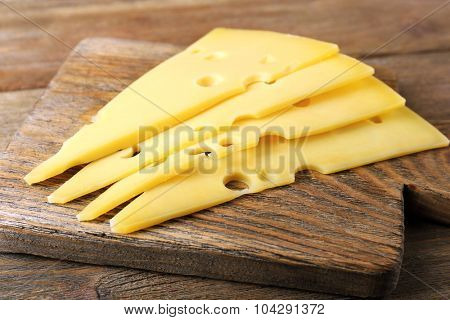 Sliced of cheese on wooden background