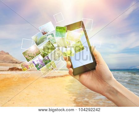 Hand holding smart phone with streaming images