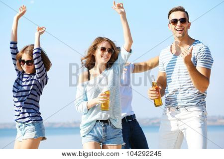 Young people with beer on the riverside