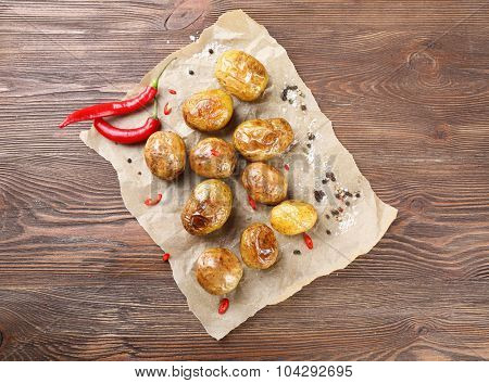 Baked spicy potatoes on parchment on wooden table, top view