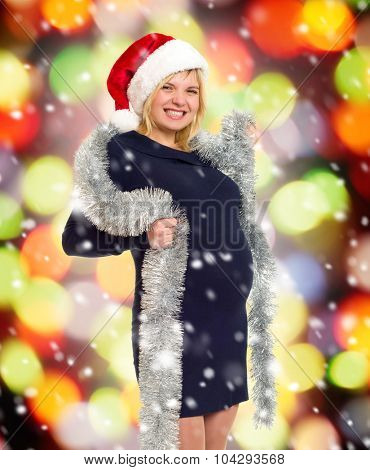 christmas holiday pregnant woman in santa hat on colorful background with snow