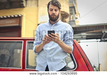 Handsome man sending a text message
