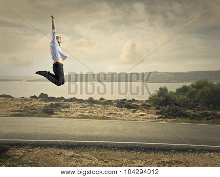 Happy man jumping in a solitary road