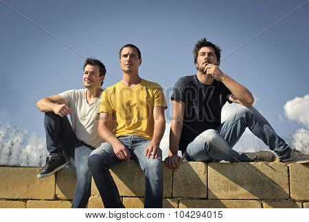 Three friends sitting together staring in the distance
