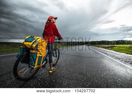 Lady traveler with loaded bicycle standing on the wet asphalt road