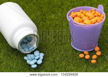 White bottle of blue pills and buckets filled with orange tablets