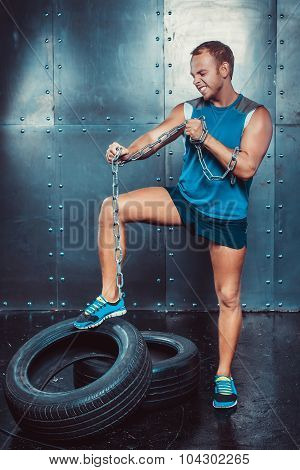 Sportsmen. Fit Malestands With One Foot On The Tire Iron Chain And Tears , Concept  Fitness