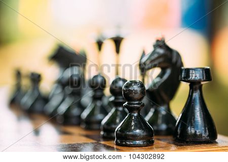 Black Old Chess Figures Standing On Chessboard