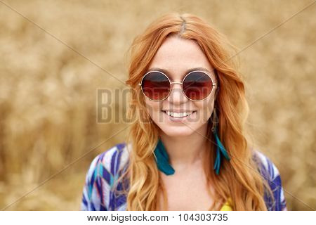 nature, summer, youth culture and people concept - smiling young redhead hippie woman in sunglasses outdoors