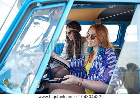 summer holidays, road trip, vacation, travel and people concept - smiling young hippie women driving in minivan car