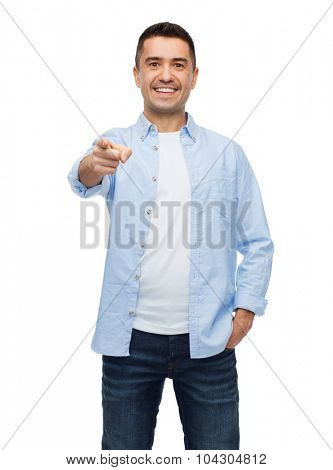 happiness, gesture and people concept - smiling man pointing finger on you