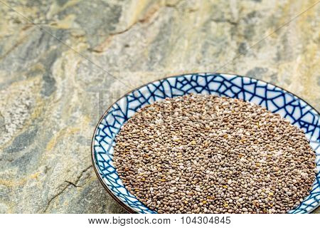 ceramic bowl of chia seeds against slate stone background