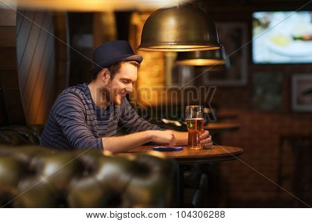 people and technology concept - happy man with smartphone drinking beer and reading message at bar or pub