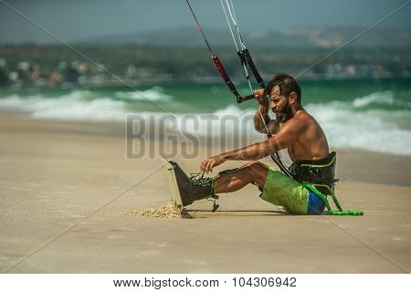 Handsome man sitting on the beach and preparing to Kitesurfing