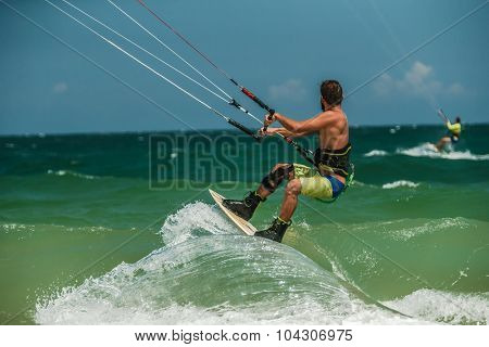 Handsome man Kitesurfing in blue sea