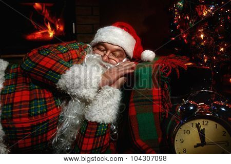 Santa Claus  sleeping at home near Christmas tree and  resting by his fireplace