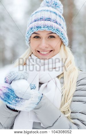 season, christmas and people concept - happy smiling young woman holding snowball in winter forest