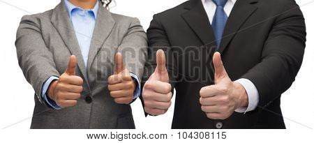 business and office concept - businessman and businesswoman showing thumbs up