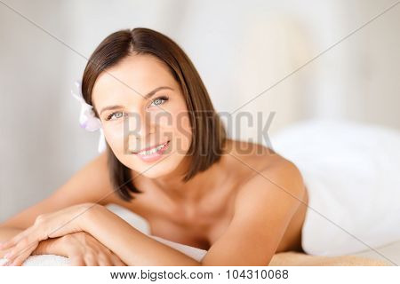health and beauty, resort and relaxation concept - beautiful woman with flower in her hair in spa salon lying on the massage desk