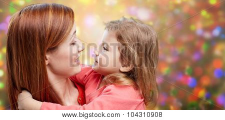 family, christmas, children and people concept - happy mother and little daughter hugging over holidays lights background